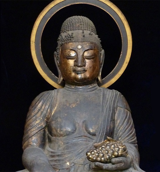 statue of Buddha holding a bunch of grapes